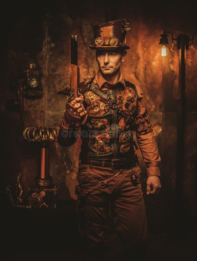 Homme de Steampunk avec l'arme à feu sur le fond de steampunk de vintage photos libres de droits