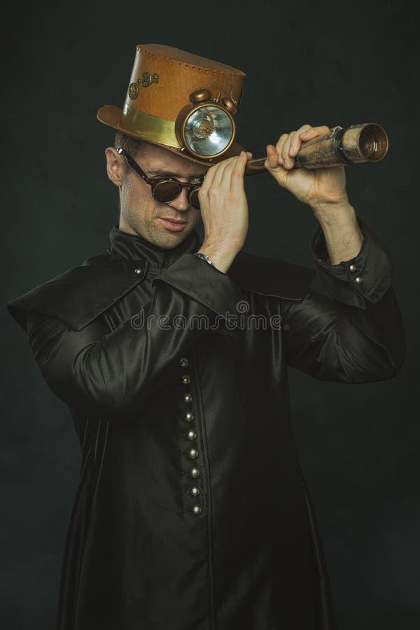 Homme de Steampunk dans un long manteau regardant par un télescope photos libres de droits