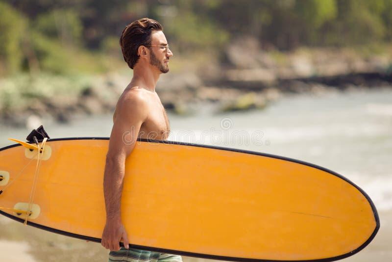Homme de surfer avec la planche de surf sur la côte photographie stock libre de droits