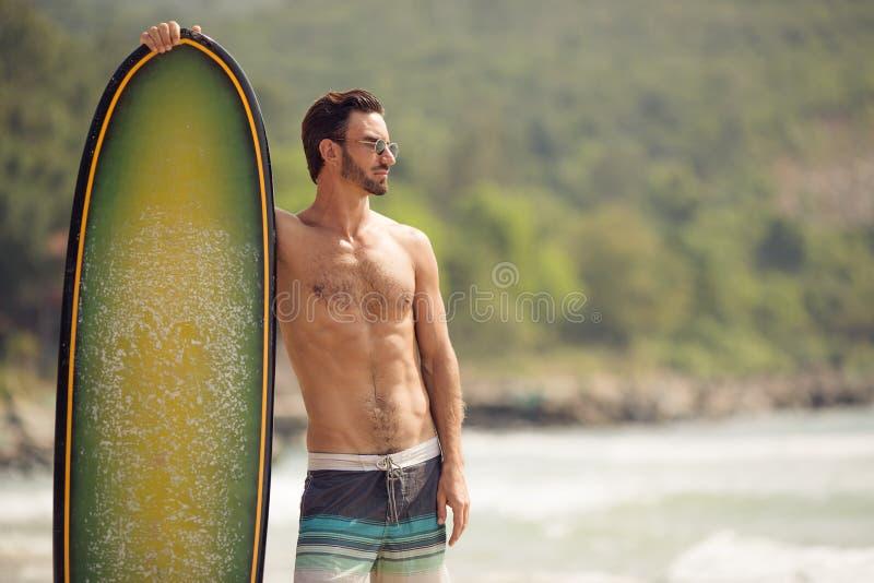 Homme de surfer avec la planche de surf sur la côte image libre de droits