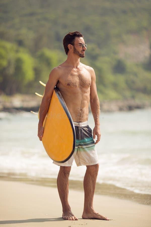 Homme de surfer avec la planche de surf sur la côte photo stock