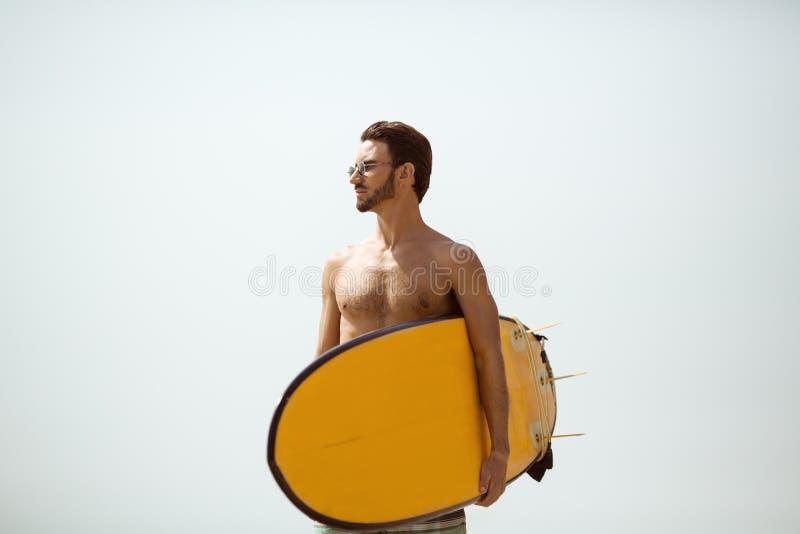 Homme de surfer avec la planche de surf sur le fond de ciel images libres de droits