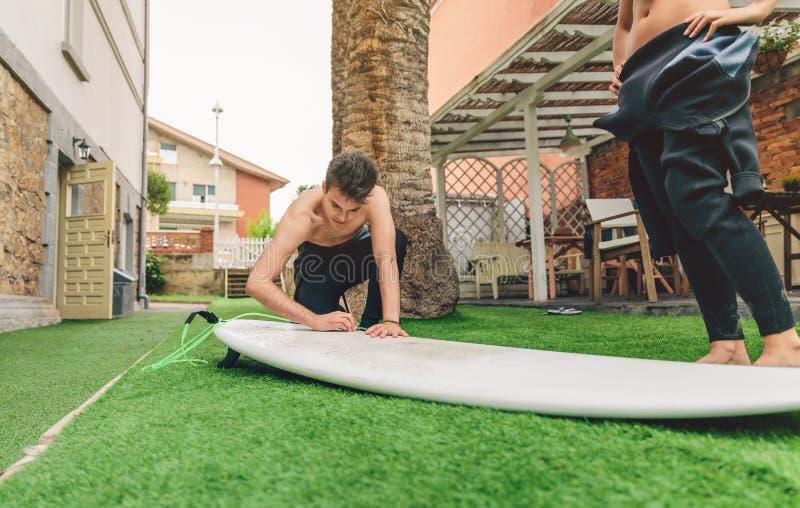 Download Homme De Surfer Avec Le Wetsuit Cirant La Planche De Surf De Femme Photo stock - Image du femelle, lifestyle: 56478450