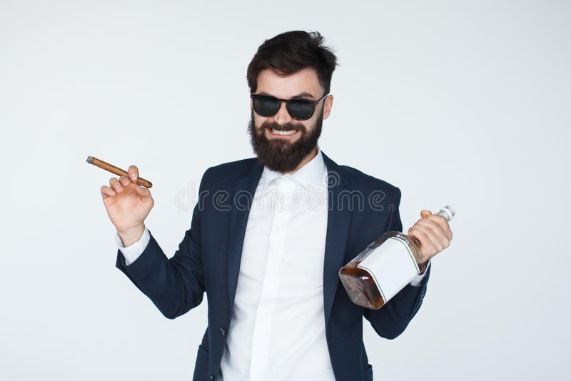 Homme de tabagisme heureux avec la boisson alcoolisée photo stock