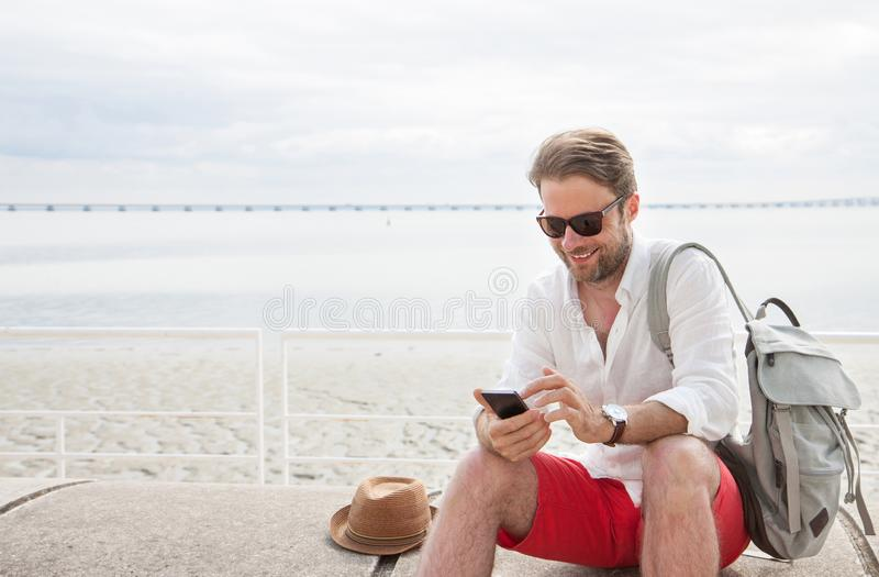 Homme de touristes avec le sac à dos regardant le téléphone portable extérieur par la mer photo libre de droits