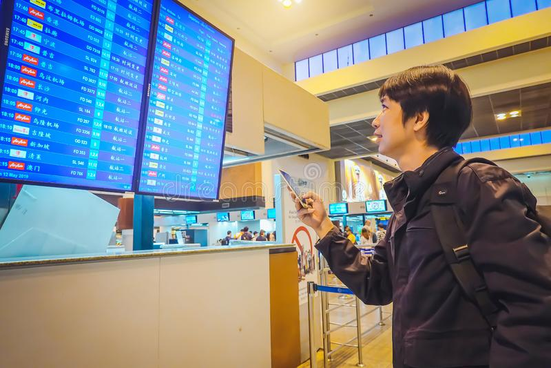 Homme de touristes dans le terminal d'aéroport international, regardant le conseil de l'information, le vérifiant vol photographie stock libre de droits
