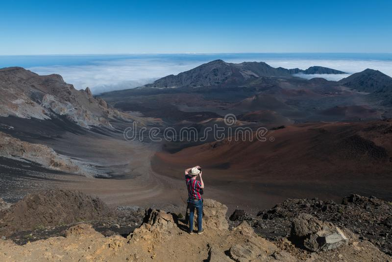 Homme de touristes prenant des photos de vallée de montagne de volcan à partir du dessus sur la grande île, Hawaï image stock