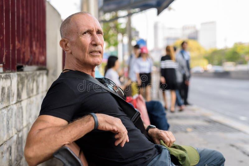 Homme de touristes supérieur chauve attendant et s'asseyant sur le banc en bois à t images stock