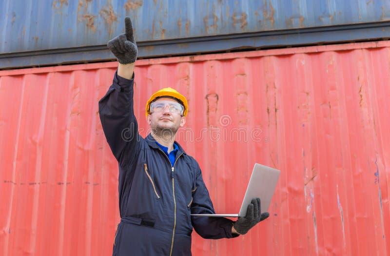 Homme de travail dans un gilet de sécurité tenant un ordinateur portable et pointant vers le ciel, Foreman commande conteneur de  photo libre de droits