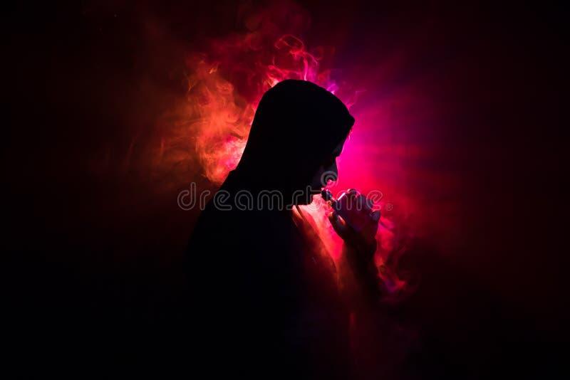 Homme de Vaping tenant un mod Un nuage de vapeur Fond noir Vaping une cigarette électronique avec de la beaucoup de fumée Concept image stock