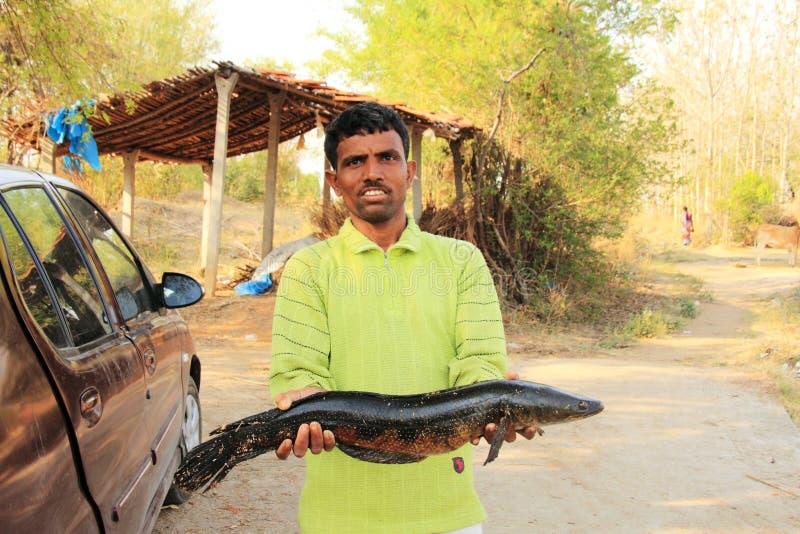 Homme de village tenant des poissons photos stock