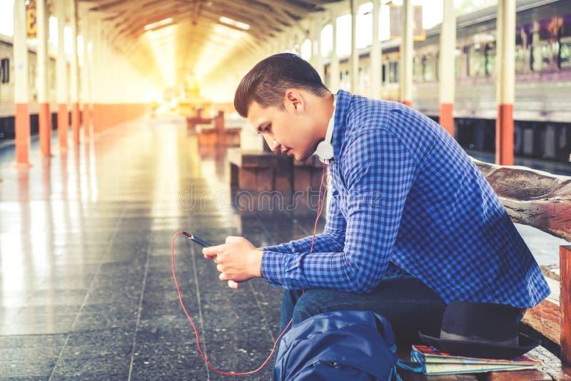 Homme de voyage à l'aide du téléphone portable à la station de train image stock