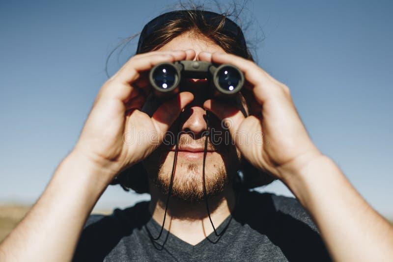 Homme de voyageur à l'aide des jumelles avec le voyage photographie stock