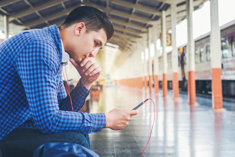 Homme de voyageur à l'aide du train de attente de comprimé et de téléphone sur le sta images stock