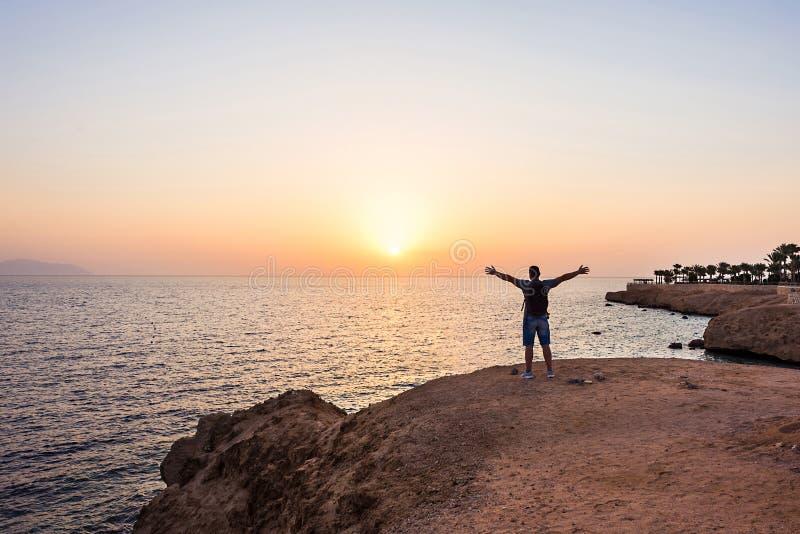 Homme de voyageur avec le sac à dos sur la plage au-dessus du fond de lever de soleil image stock