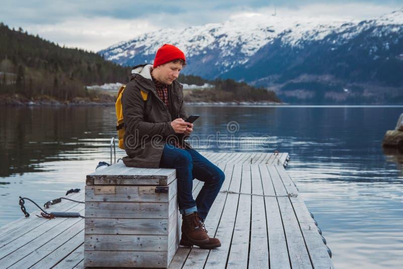 Homme de voyageur examinant le t?l?phone Touriste dans le sac ? dos jaune se reposant sur un fond d'une montagne et d'un lac a photos libres de droits