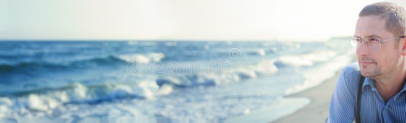 Homme de vue panoramique d'océan de panorama pensant ou méditant photo stock