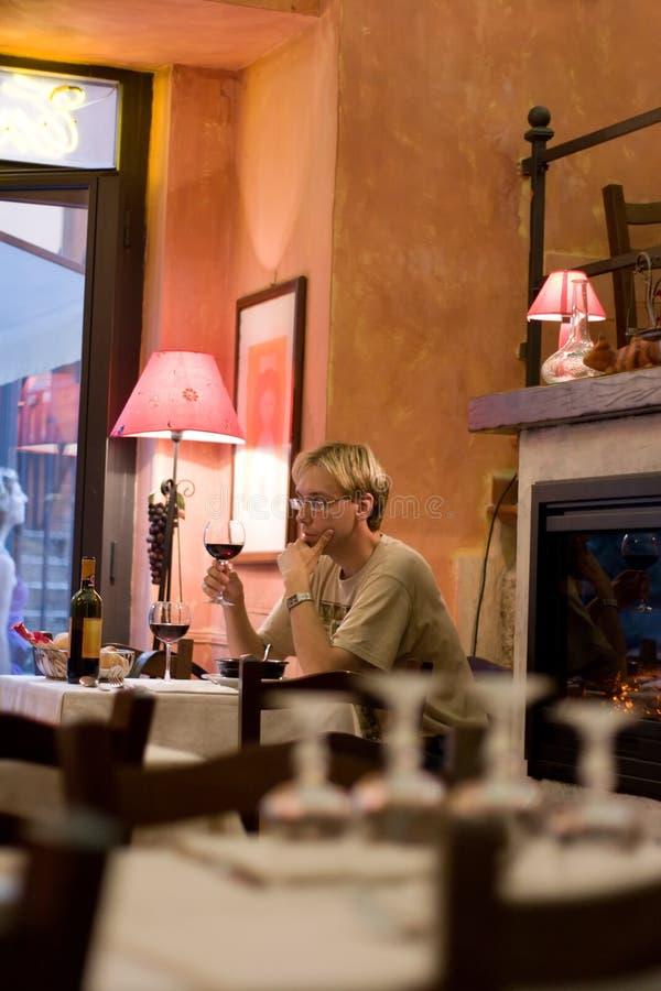 Homme de Youing goûtant le vin rouge dans le restaurant images libres de droits