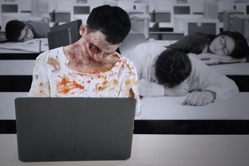 Homme de zombi avec ses amis travaillant des heures supplémentaires photographie stock libre de droits