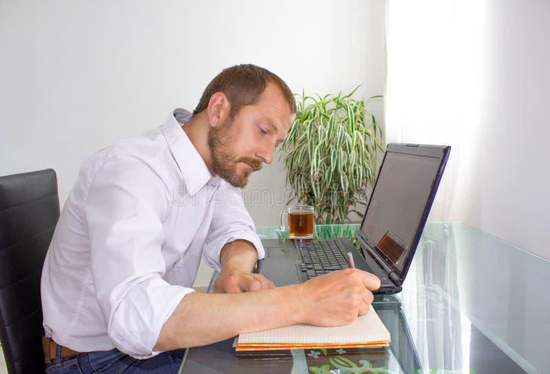 Homme derrière l'ordinateur portable au travail photo libre de droits