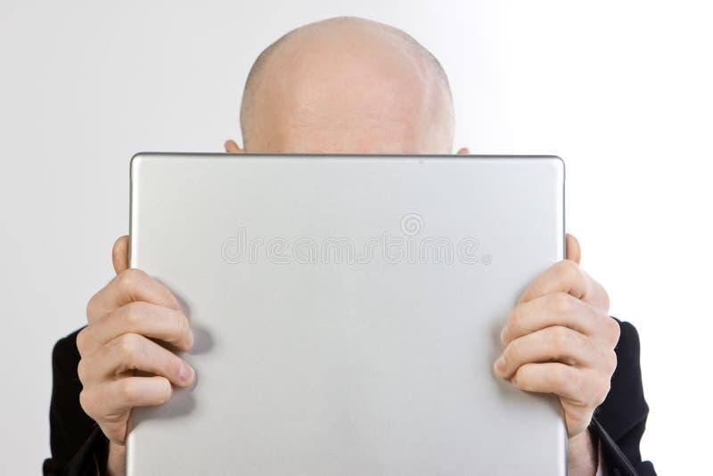 Homme derrière l'ordinateur portatif photographie stock libre de droits