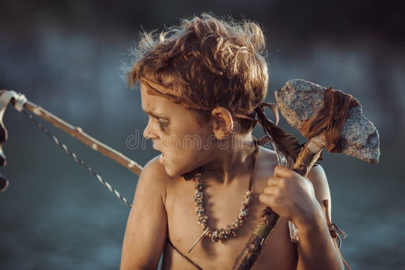Homme des cavernes, garçon viril avec l'arme primitive chassant dehors Guerrier préhistorique antique Regard héroïque de film photos stock