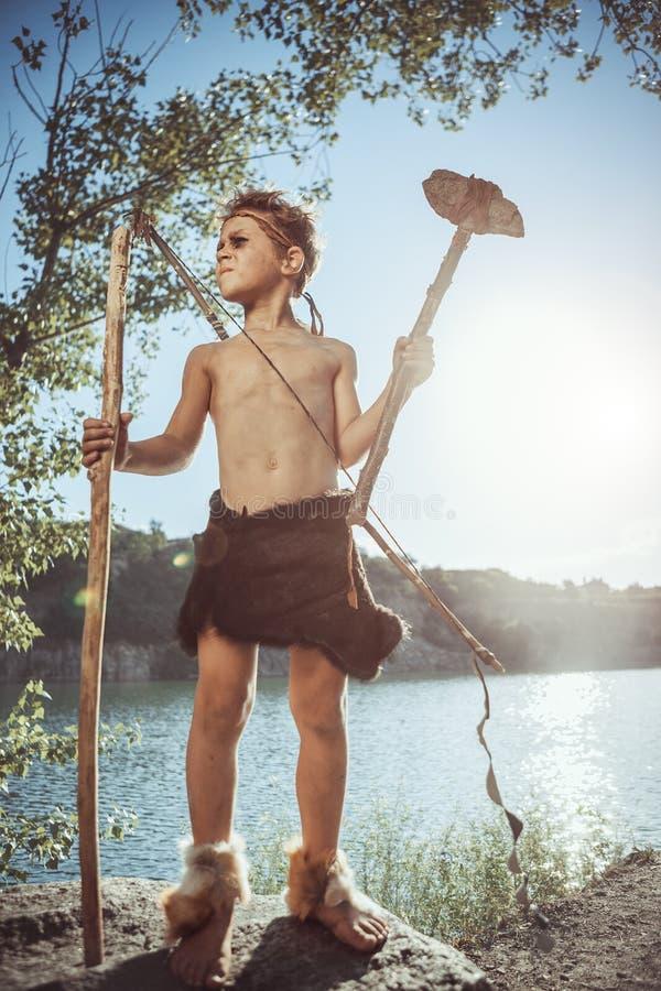 Homme des cavernes, garçon viril avec la hache en pierre et chasse d'arc photos stock