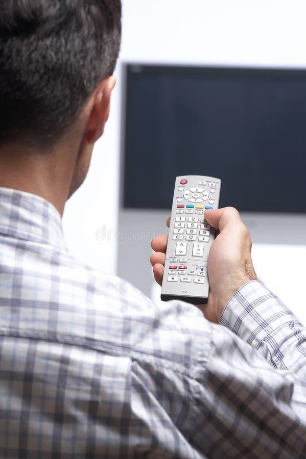 Homme devant le canal de commutation de TV photo libre de droits