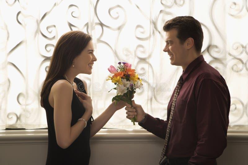 Homme donnant des fleurs de femme. images libres de droits
