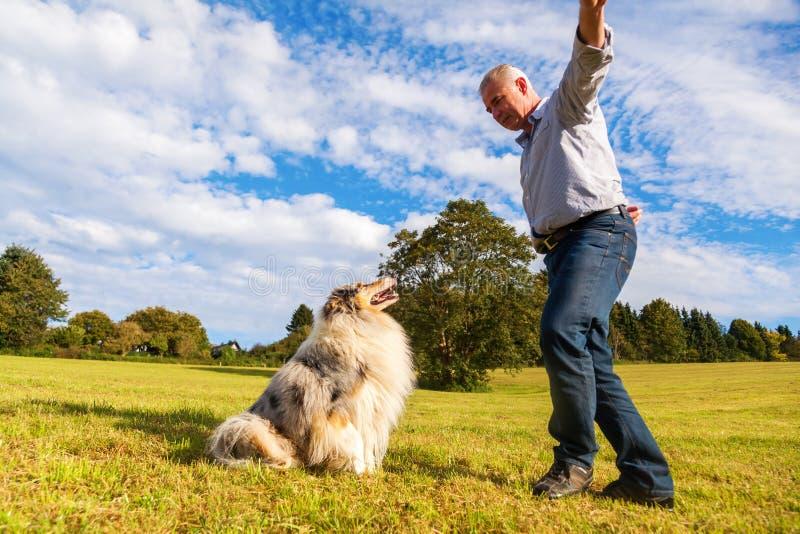 Homme donnant l'instruction à son chien photographie stock libre de droits