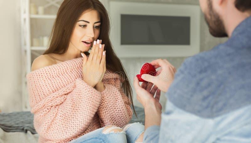 Homme donnant la bague de fiançailles à la femme étonnée à la maison photographie stock