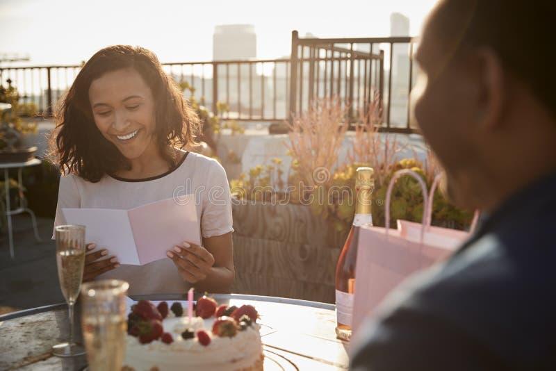 Homme donnant le cadeau de femme et carte comme ils célèbrent sur la terrasse de dessus de toit avec l'horizon de ville à l'arriè photographie stock