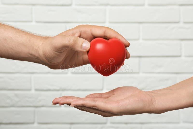 Homme donnant le coeur rouge à la femme au mur de briques blanc Concept de donation image stock