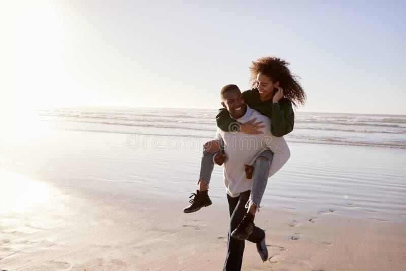 Homme donnant le ferroutage de femme des vacances de plage d'hiver images libres de droits