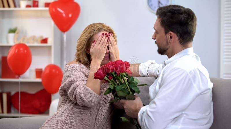 Homme donnant le groupe assez étonné de dame de roses rouges, célébrant le jour de valentines photographie stock