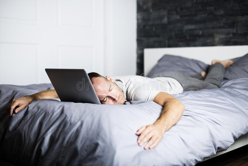 Homme dormant au-dessus de l'ordinateur portable dans le lit photo libre de droits