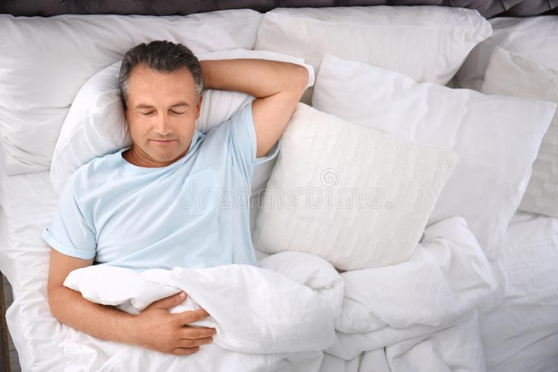 Homme dormant sur l'oreiller confortable dans le lit photographie stock