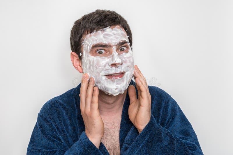 Homme drôle avec le masque crème blanc naturel sur son visage image libre de droits