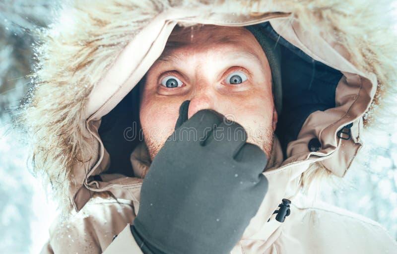 Homme drôle habillé dans le survêtement occasionnel à capuchon chaud de veste de parka avec le portrait congelé d'hiver de nez Sa images stock