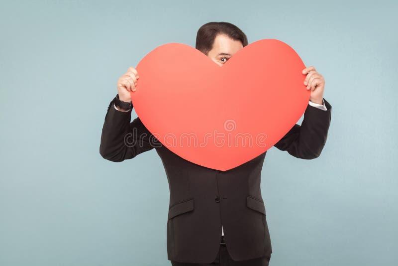 Homme drôle incognito tenant le grand coeur et regardant un oeil photographie stock libre de droits
