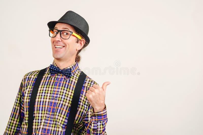 Homme drôle portant de rétros vêtements montrant le pouce sur le mur blanc, l'espace de copie L'homme excité en verres montre com photo libre de droits