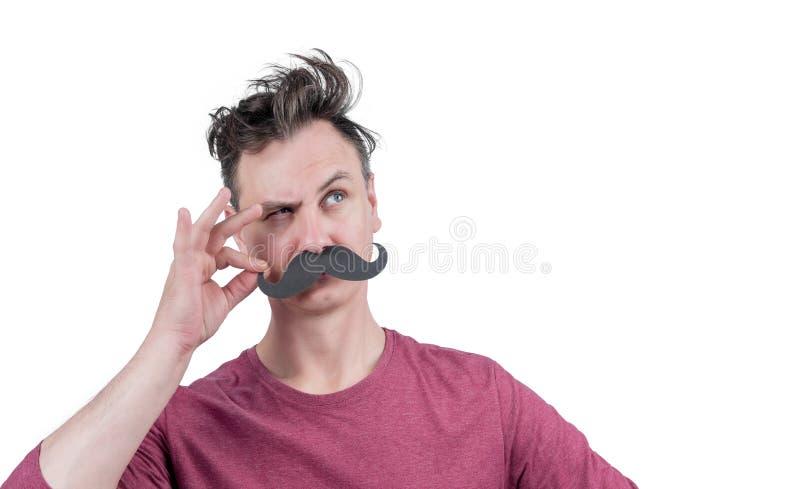 Homme drôle positif tenant ses doigts avec la moustache drôle de noir de carton, d'isolement sur le fond blanc Regardez là-bas ! photos stock