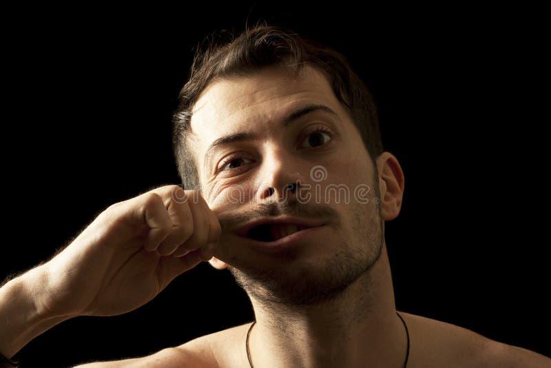 Homme drôle qui tire sa joue photos stock