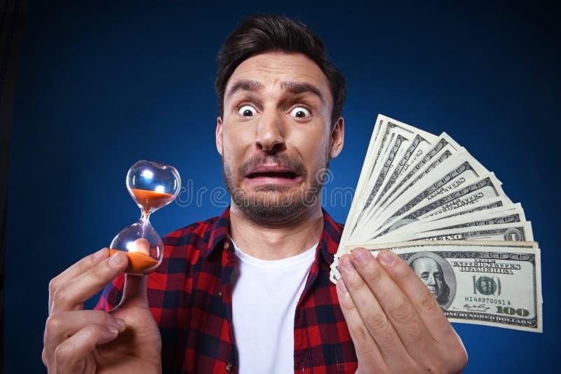 Homme drôle tenant l'argent liquide et le sablier photo libre de droits