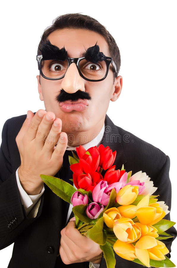 Homme drôle avec des fleurs d'isolement sur le blanc photographie stock