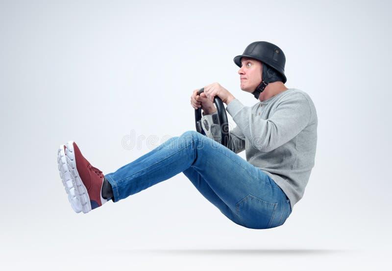 Homme drôle dans le conducteur de voiture de casque avec le volant Le fichier contient un chemin à l'isolement photographie stock libre de droits