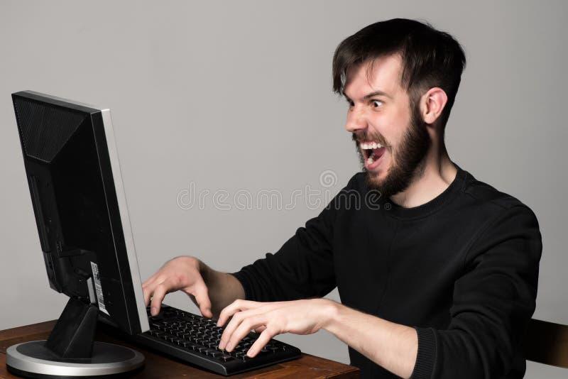 Homme drôle et fol à l'aide d'un ordinateur photographie stock