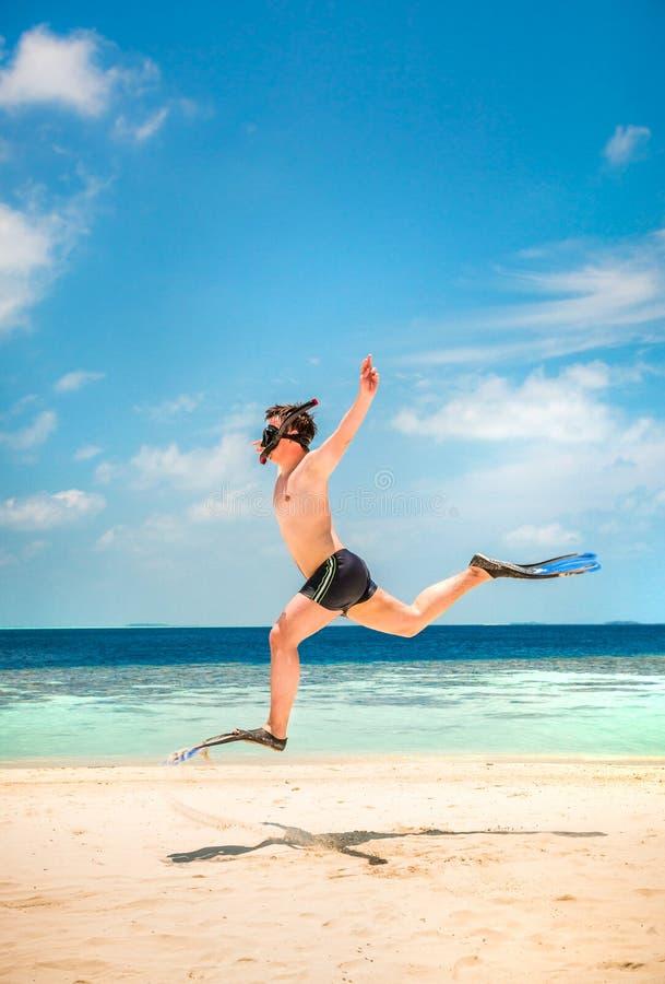 Homme drôle sautant dans les nageoires et le masque. photo libre de droits