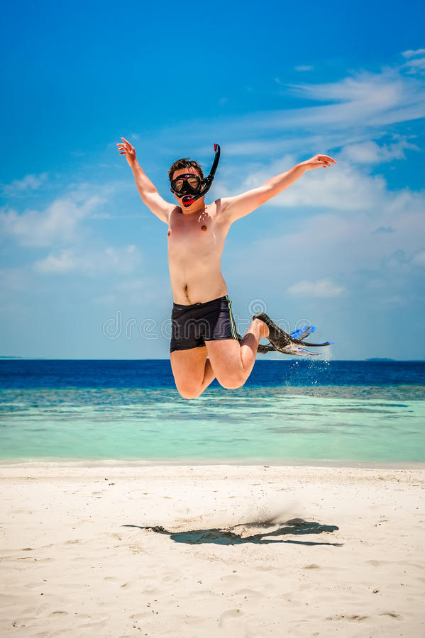 Homme drôle sautant dans les nageoires et le masque photos stock