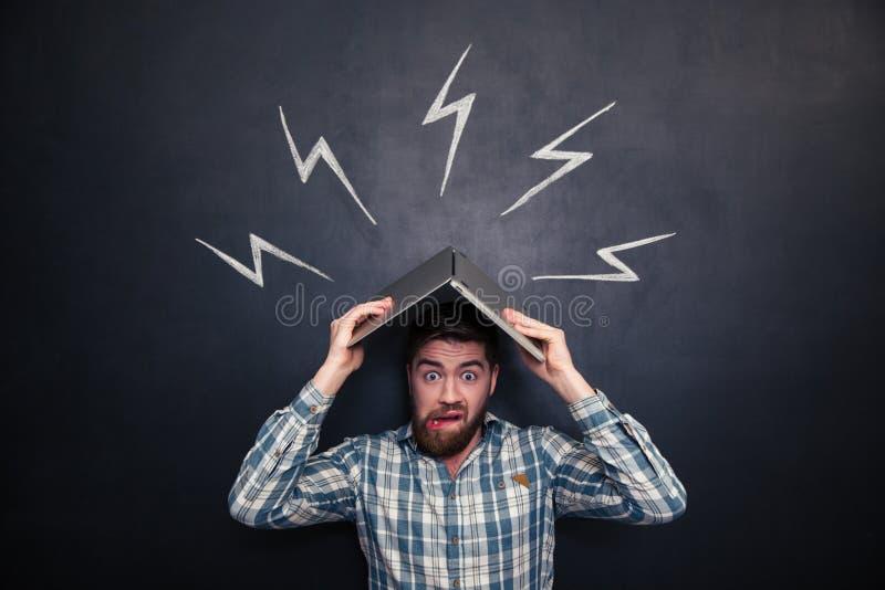 Homme drôle tenant l'ordinateur portable au-dessus de la tête au-dessus du fond du tableau images stock